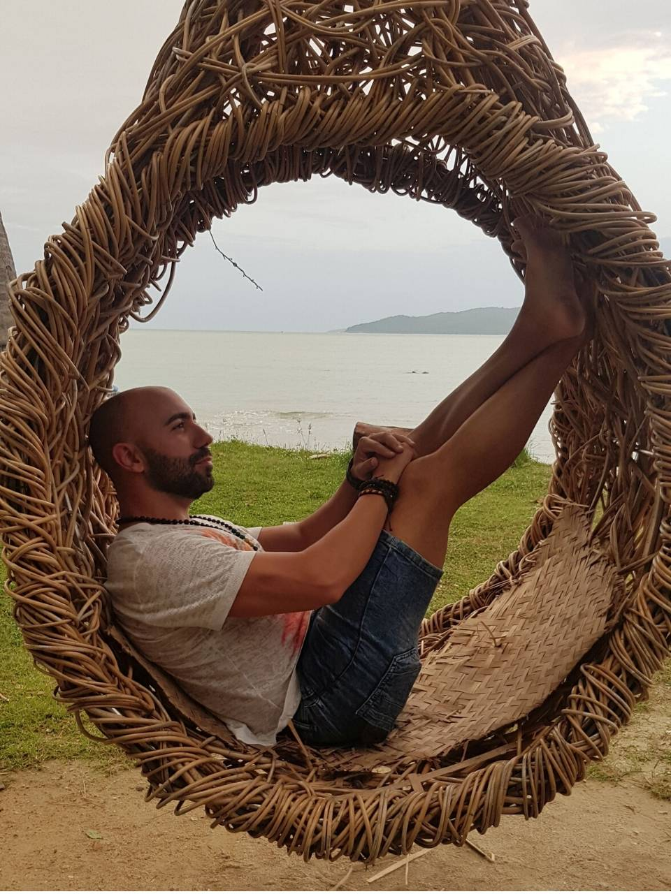 Mauro Federici sitting on a seesaw in the shape of a nest on Koh Samui beach