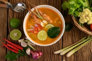 Tom Yum Kung Thai hot spicy soup shrimp with lemon grass, lemon, galangal and chilli on wooden background Thailand Food